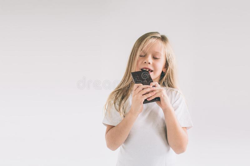 Young child eating a chocolate bar. Blondy girl isolated on white background. stock images