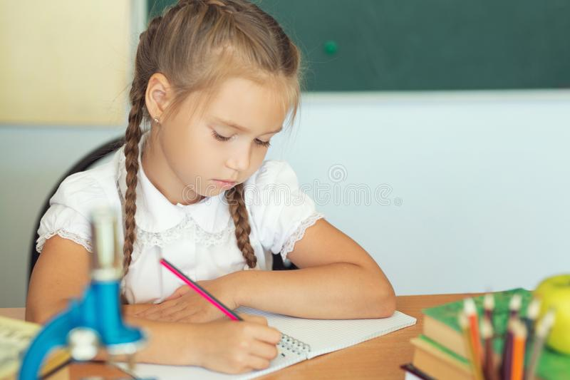 Young child girl drawing or writing with colorful pencils in notebook in school over blackboard.  stock image