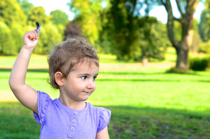 Download Young Child, Girl, Toddler, Holding A Feather High As She Plays In The Park. Stock Photo - Image: 33622416
