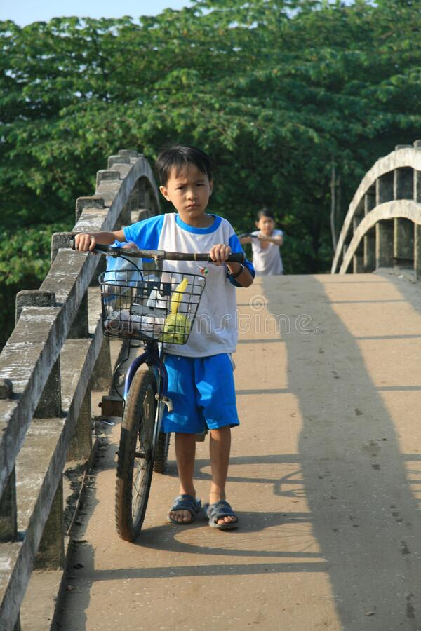 Young child with large bike. A young child stands next to his too big bike on a bridge on his way to school
