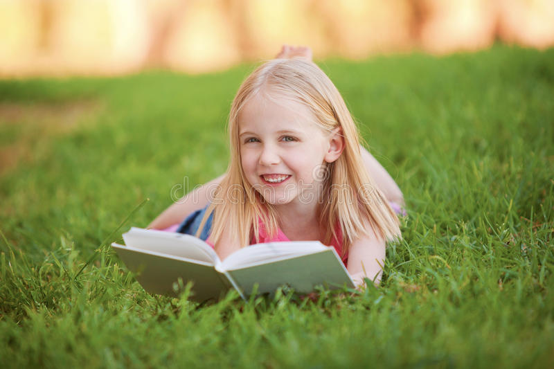 A young child lying on the grass reading a book royalty free stock image