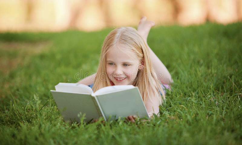 A young child lying on the grass reading a book royalty free stock photography