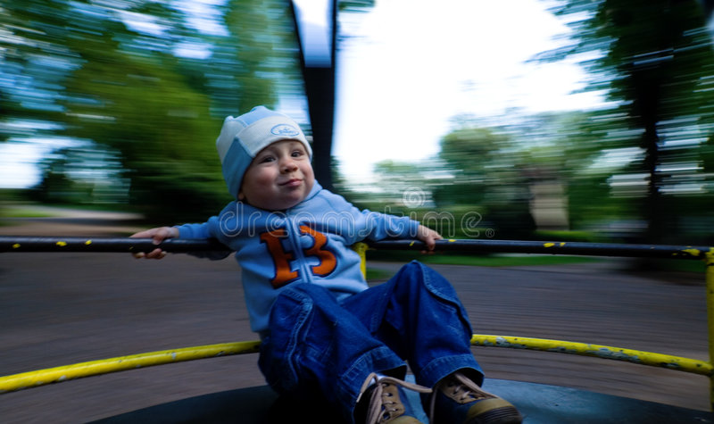 Young child on merry-go-round stock photos