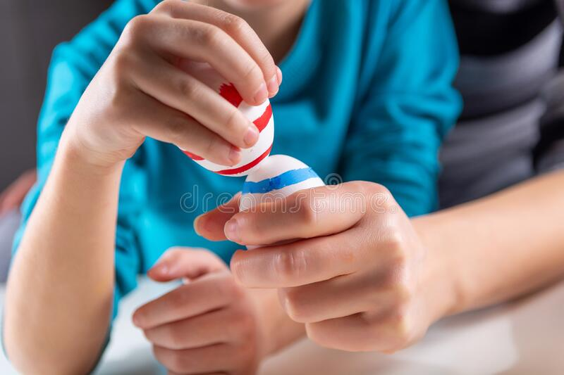Child hands with colored Easter eggs knocking stock image