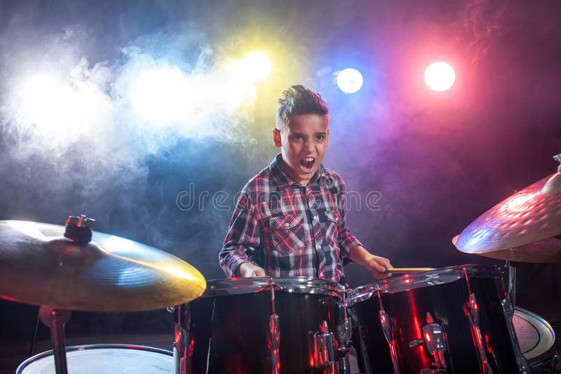 Drummer playing the drums with smoke. Young child musician playing the drums stock image