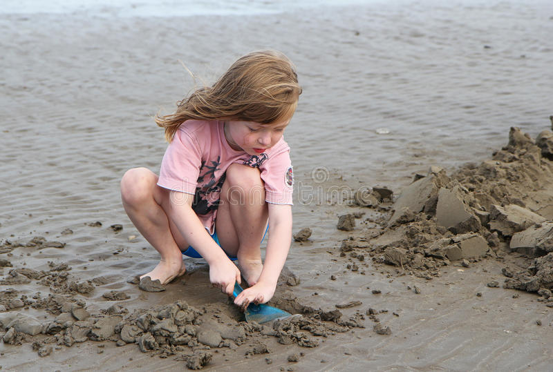 Young child playing, making sandcastles on a beach royalty free stock image