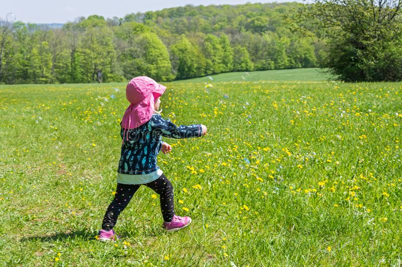 Young child is playing on summery flower meadow with soap bubbles royalty free stock photography