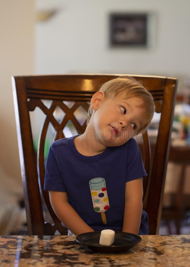 Free Young Child Sitting At A Table Waiting Patiently For A Marshmallow Stock Photo - 168445650