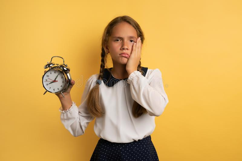 Young child student with ringing alarm clock is lazy going to school. Yellow background stock photo