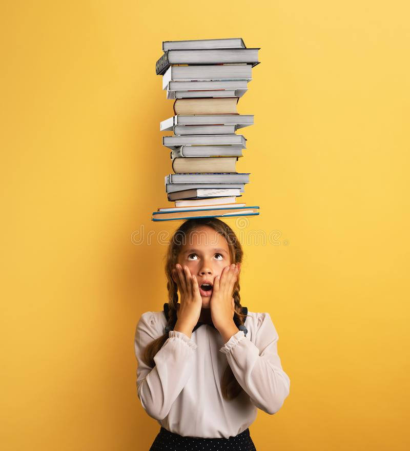 Young child student worried due to too much books to read and study. Yellow background stock photo
