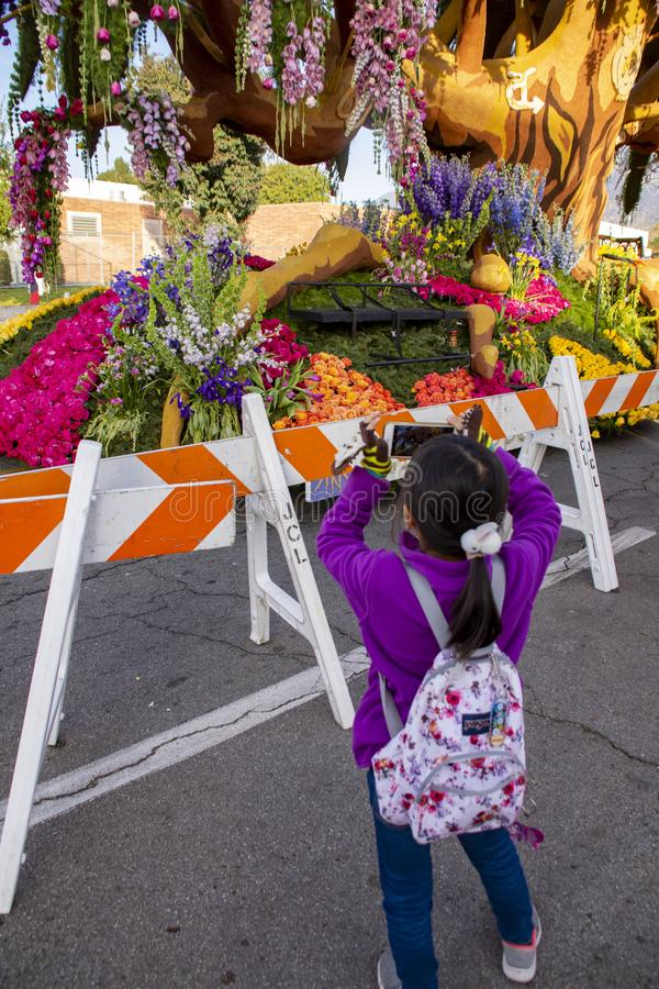 Young child taking a picture of a Rose Parade Float royalty free stock image
