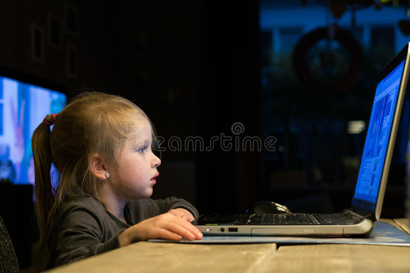 Young child is using an laptop stock image