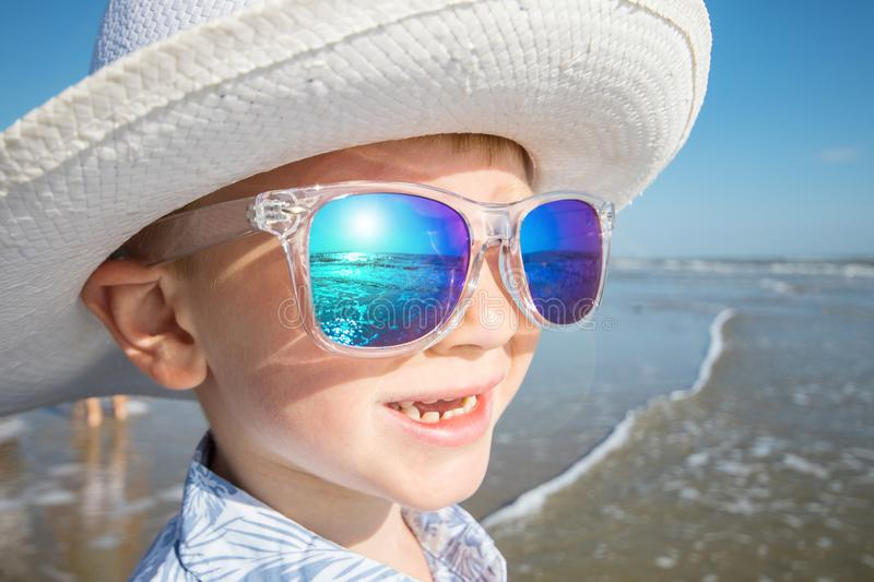 Young child watch the sun wearing hat and sunglasses stock photography