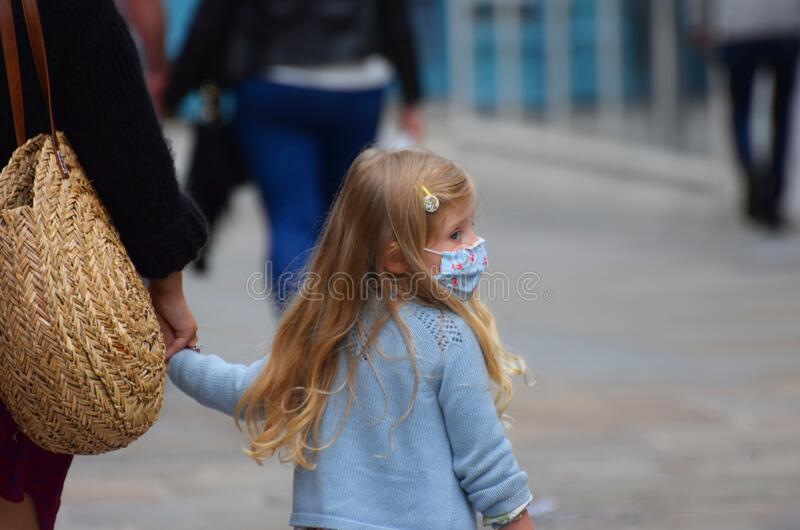 A young child wearing a face mask in public on the weekend that wearing face coverings became law in England stock photo