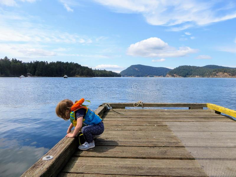 A young child wearing her life jacket on a dock looking for fish with a beautiful scenic background behind her. She is having fun stock image