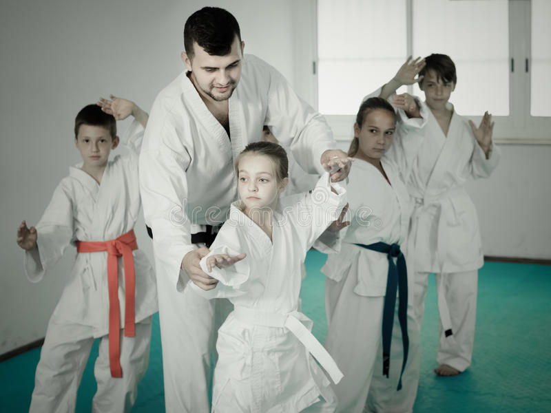 Young children doing karate kicks with male coach royalty free stock image