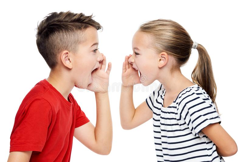 Young children facing eachother and shouting. Speech therapy concept over white background. royalty free stock images