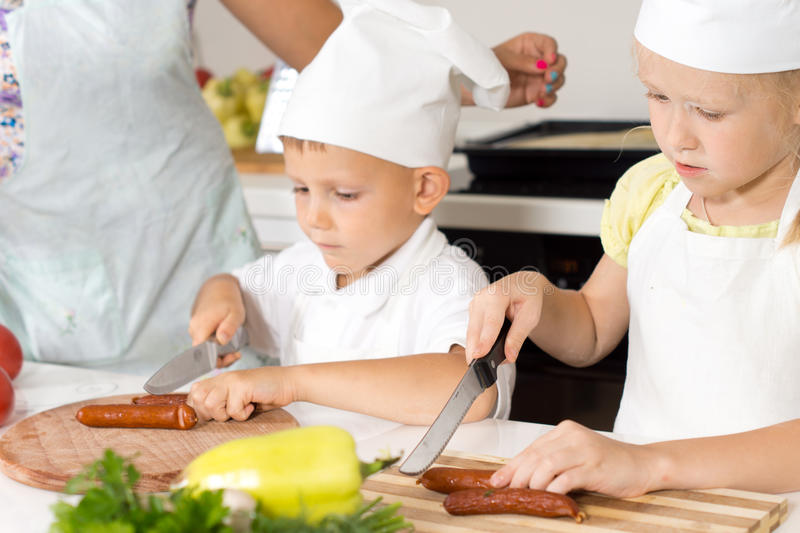 Young children learning to cook. Slicing sausages for homemade pizza under the watchful eye of their mother stock photo