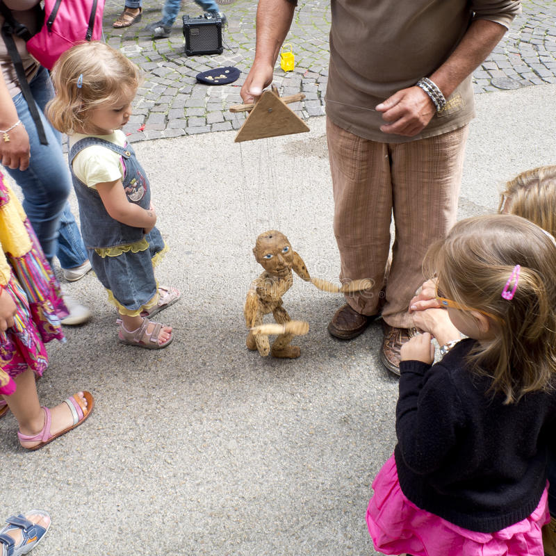 Young children look at a wooden puppet in the street. stock photography