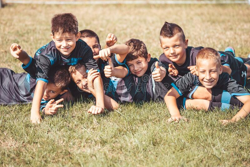 Young children players celebrating victory together while lying on grass stock image