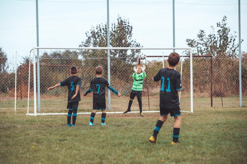 Young children players match on soccer field stock image