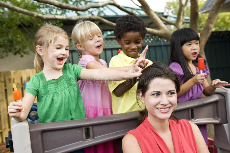 Young children playing in daycare with teacher. Diverse group of preschool 5 year old children playing in daycare with teacher royalty free stock photos