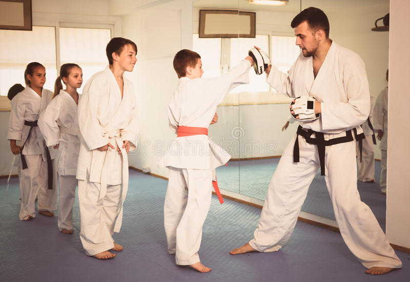 Young children are practicing on boxing paws with coach royalty free stock images