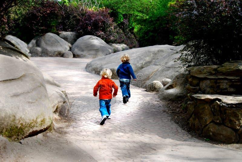 Young children running pathway rocks stock image