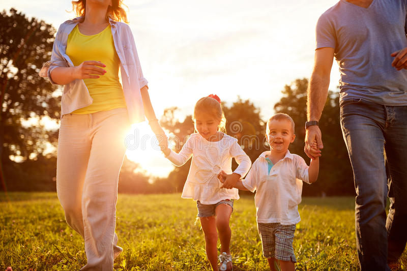Young children walking with parents in park stock photos