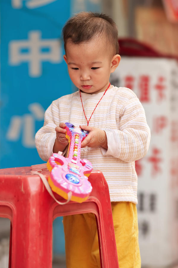 Young Chinese boy playing with his plastic toy, Guangzhou, China royalty free stock photography