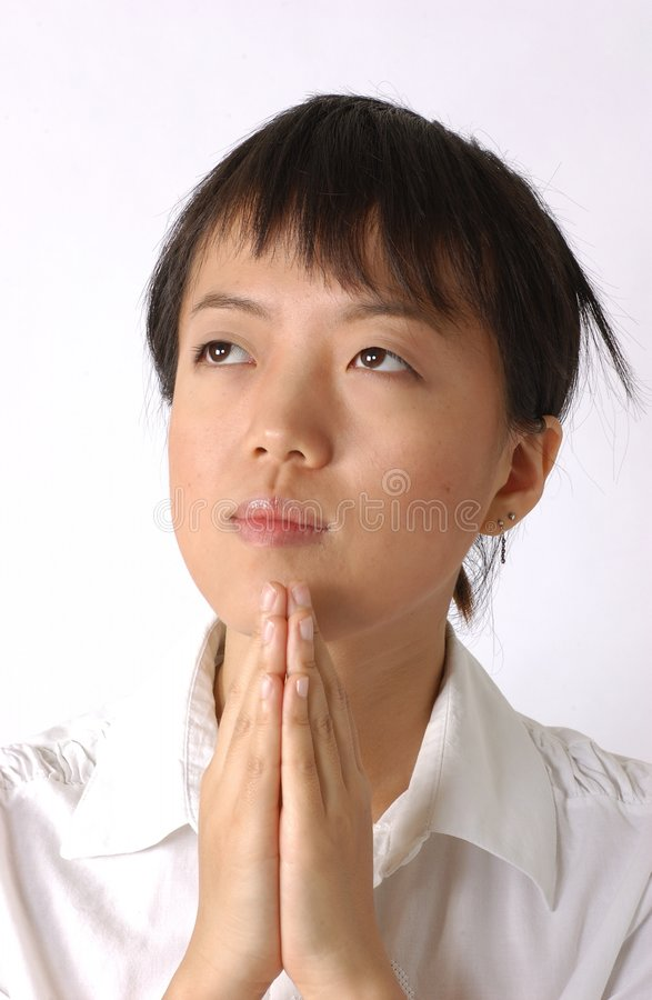 Young chinese girl. A you chinese woman is praying. It seems she believes in God very strong stock image