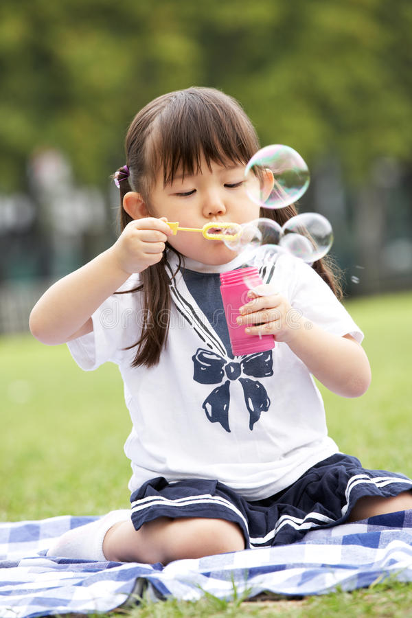Free Young Chinese Girl In Park Blowing Bubbles Stock Images - 26097924