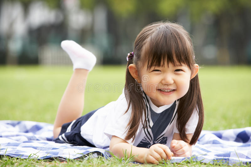 Download Young Chinese Girl Lying On Blanket In Park Stock Image - Image of having, playing: 26097923