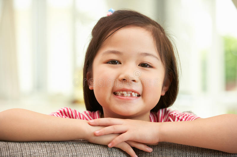 Young Chinese Girl Relaxing On Sofa At Home. Smiling At Camera stock images