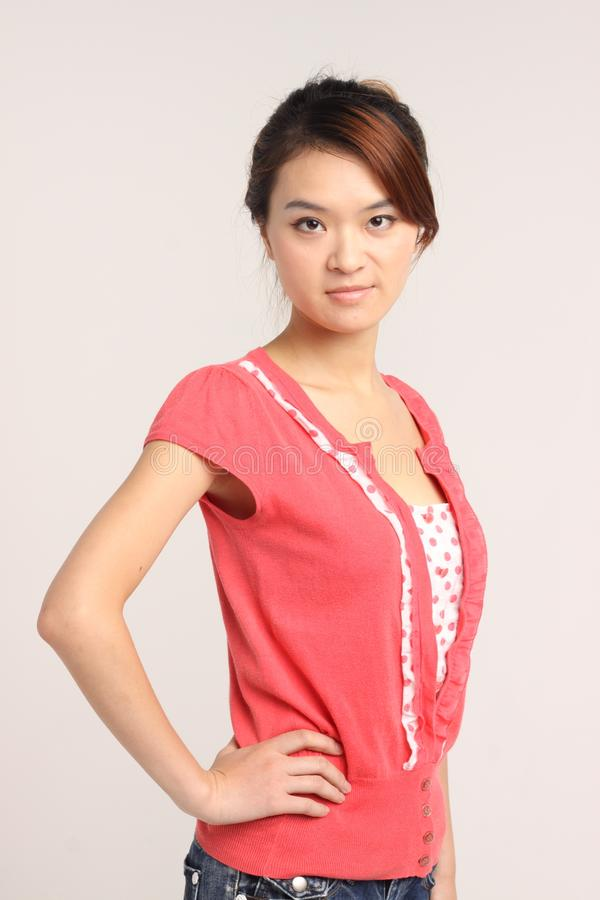 Young Chinese lady in casual attire sidepose. An young Chinese lady in casual attire standing with one hand on hip and posing sideways. Model looking into the stock photo