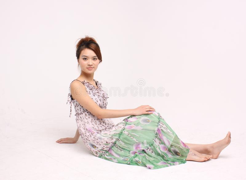 Young Chinese lady in casual attire sitting on the floor. An young Chinese lady in casual attire sitting on the floor. Full-length view of the model. Shot in a stock photo
