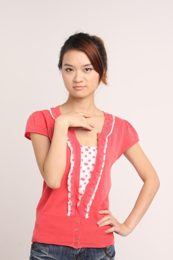 Young Chinese lady in casual attire. An young Chinese lady in casual attire standing with one hand on hip and another hand below her neck. Model looking into the royalty free stock photography