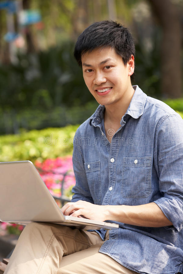 Young Chinese Man Using Laptop Whilst  Relaxing Royalty Free Stock Photos