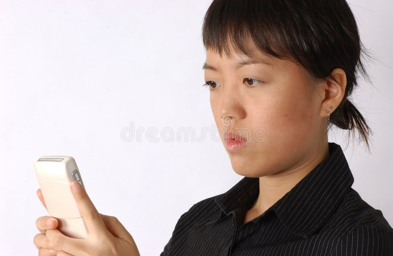 Young chinese woman. You chinese woman using a mobile and seems surprised royalty free stock image