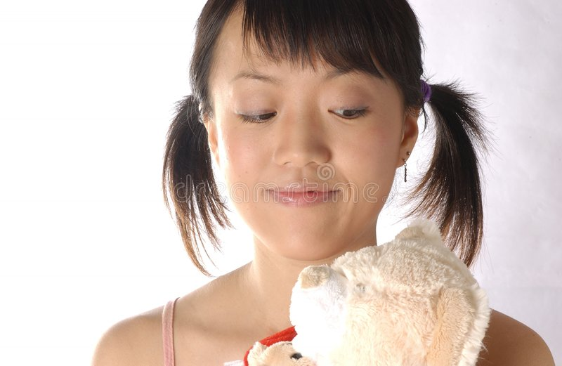 Young chinese woman. Young chinese girl looking at her Tebby bear royalty free stock photography