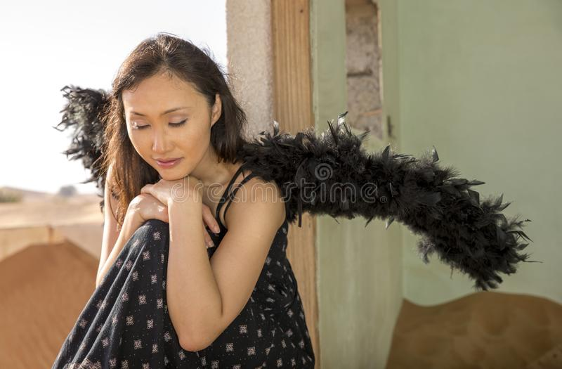Young chinese woman with black wings in a desert stock image