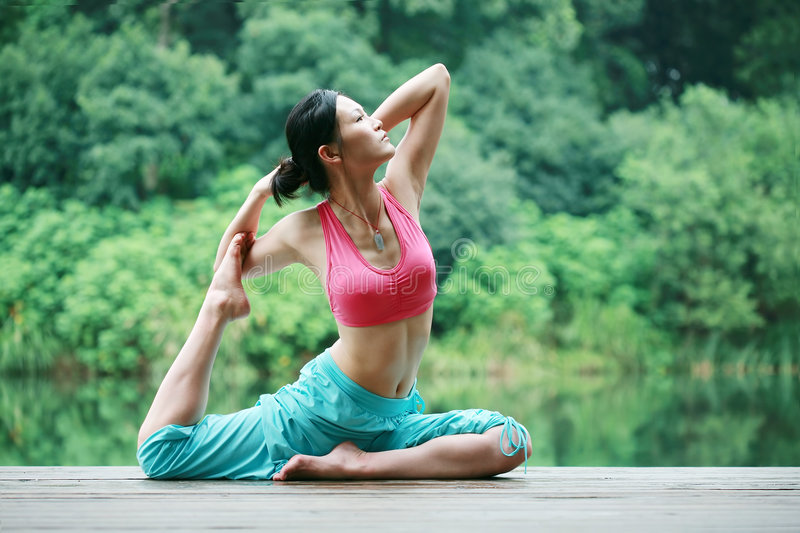 Young chinese woman practicing yoga outdoor royalty free stock image