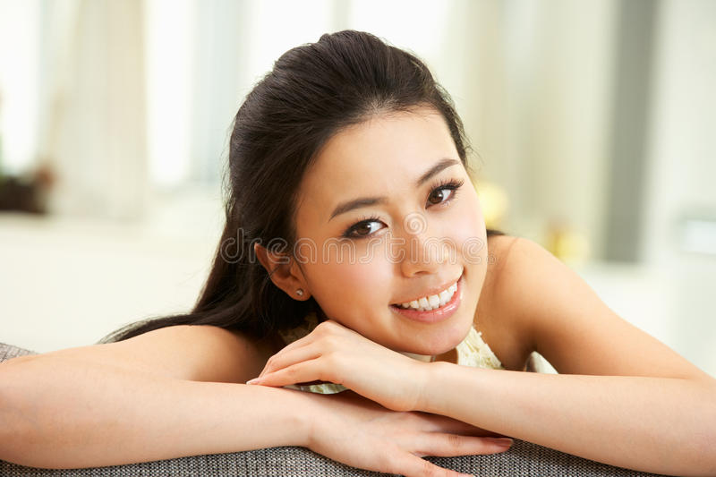 Young Chinese Woman Relaxing On Sofa At Home Stock Photo
