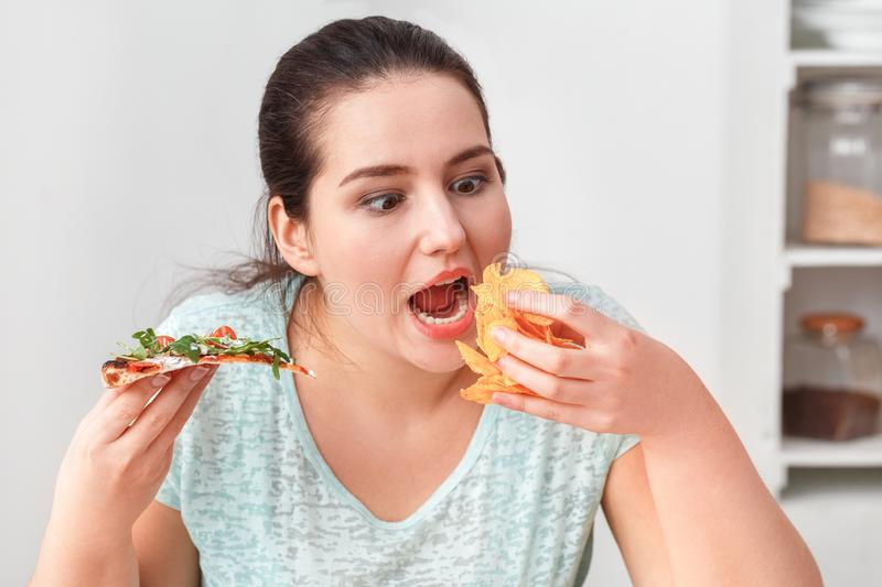 Binge Eating. Chubby girl sitting at kitchen table eating pizza and chips hungry close-up. Young chubby woman sitting at table in kitchen binge eating eating stock images