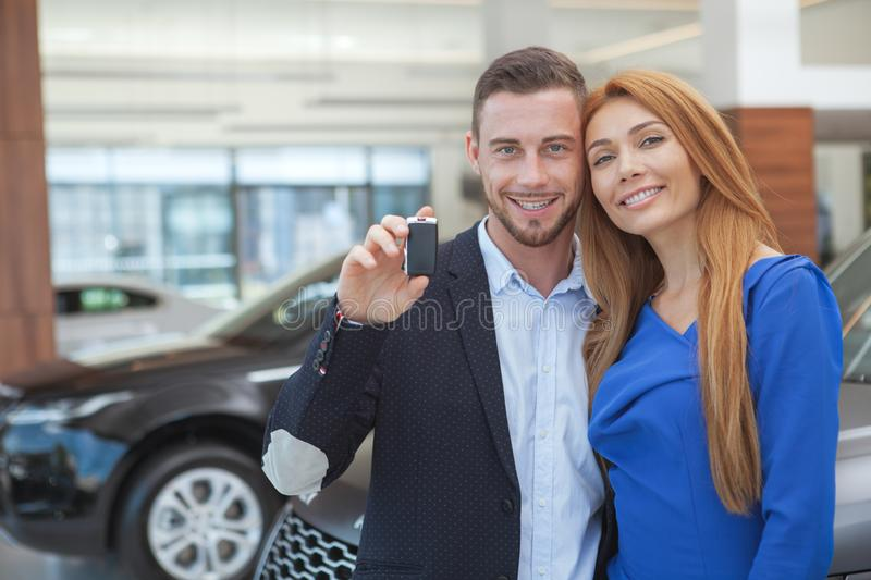 Young classy couple buying luxurious car at the dealership. Beauitful happy elegant couple hugging, smiling to the camera after buying new car. Handsome men royalty free stock image