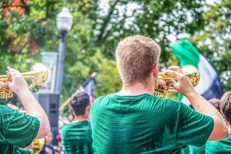 Young clean cut men in sweaty green t shirts play trumpets in parade with bokeh trees and American flag in background - back view stock photo