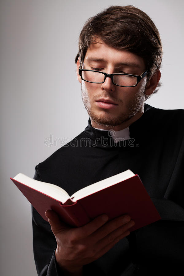 Young clergyman studying a Bible stock photo