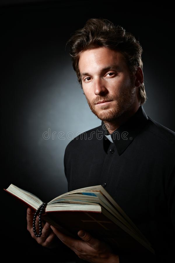 Young cleric holding holy Bible royalty free stock photography