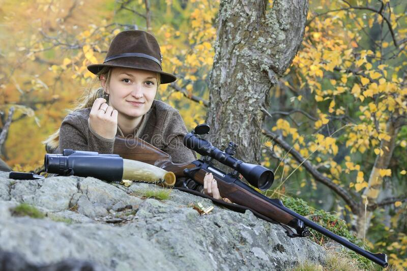 Young, Clever Woman Deer Hunter wearing green uniform with Rifle on the rock in Background autumn trees. Forest, hunting, deer, gun stock photography