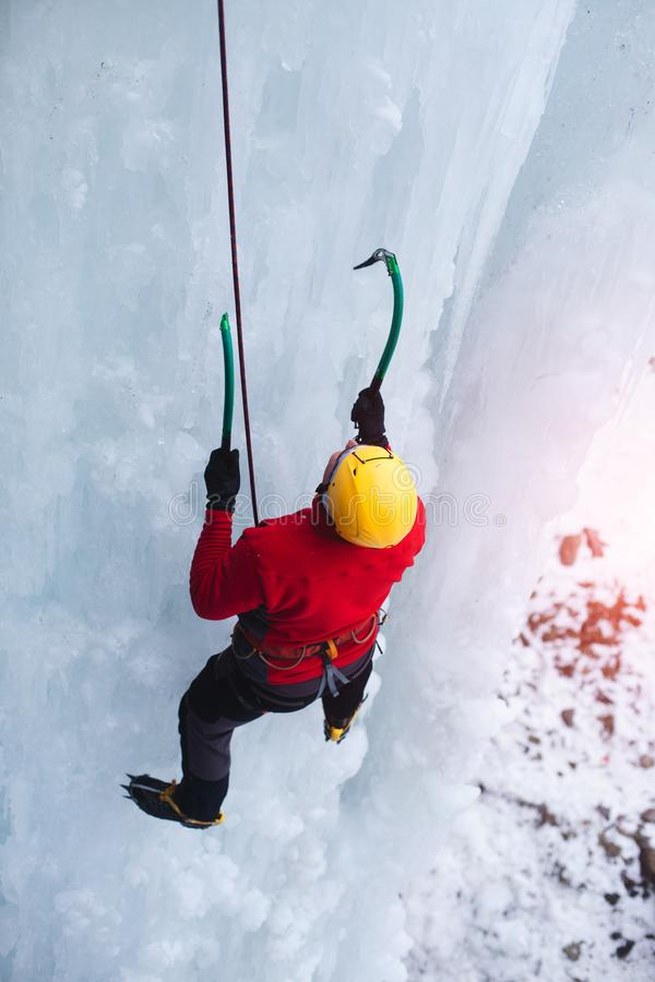 The climber climbs on ice. A young climber climbs on ice climbing and winter sport activities in cold weather stock images